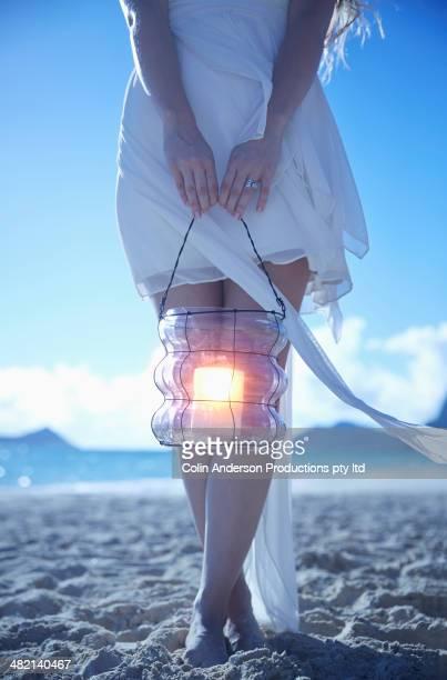 Caucasian woman carrying lantern on beach