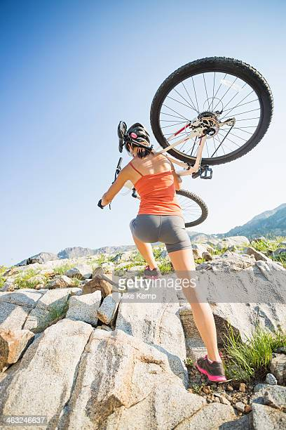 Caucasian woman carrying mountain bike on rocky hillside