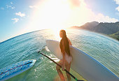 Caucasian woman carrying paddle board on beach