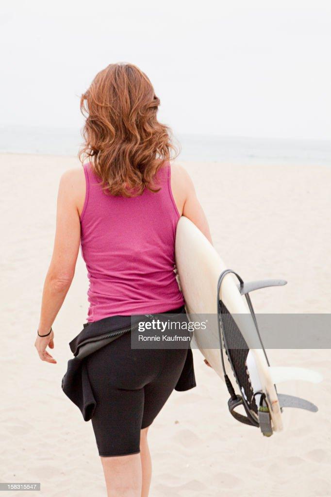 Caucasian woman carrying surfboard : Stock Photo
