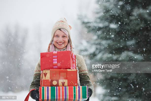 Caucasian woman carrying wrapped gifts in snow