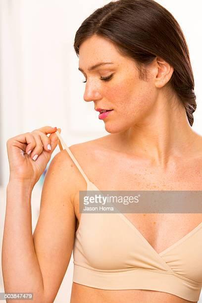 Caucasian woman checking bra straps