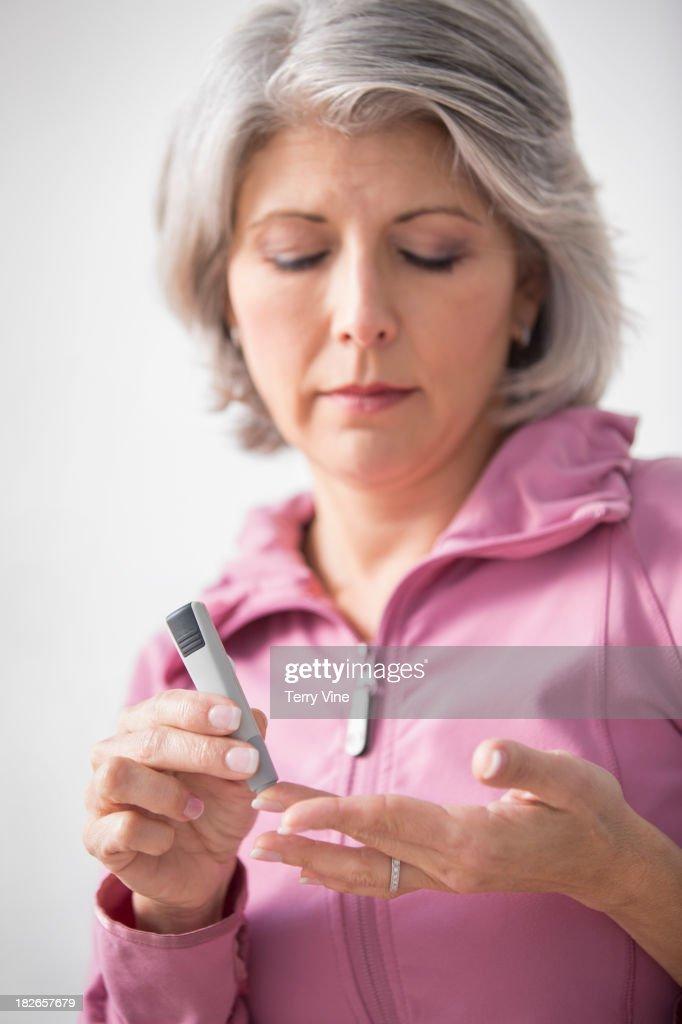 Caucasian woman checking her blood sugar
