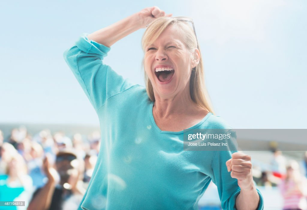 Caucasian woman cheering at sporting event : Stockfoto