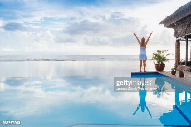 Caucasian woman cheering near swimming pool