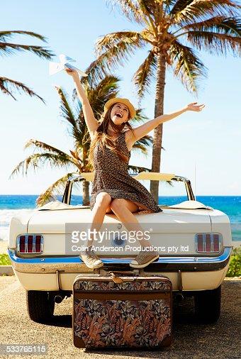 Caucasian woman cheering on convertible on beach