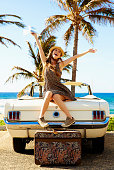 Caucasian woman cheering on convertible on beach