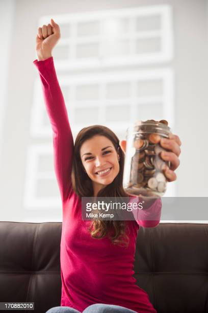 Caucasian woman cheering with jar of change