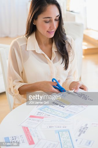 Caucasian woman clipping coupons