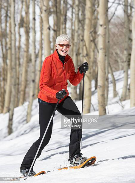 Caucasian woman cross-country skiing on hill