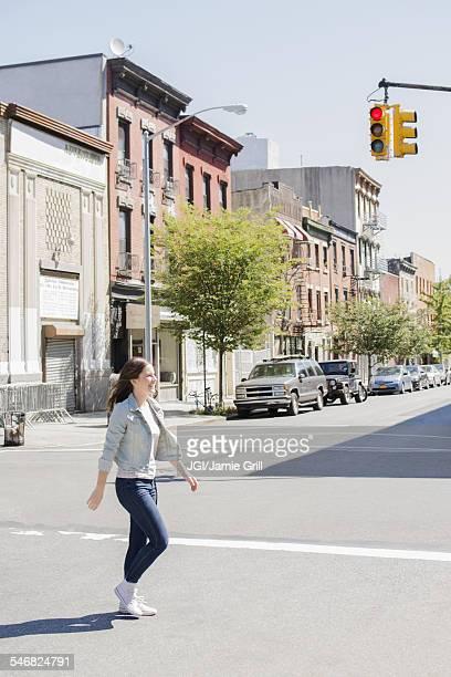 Caucasian woman crossing urban street
