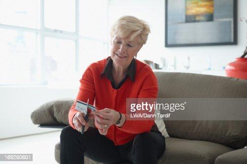 Caucasian woman cutting credit card : Stock Photo