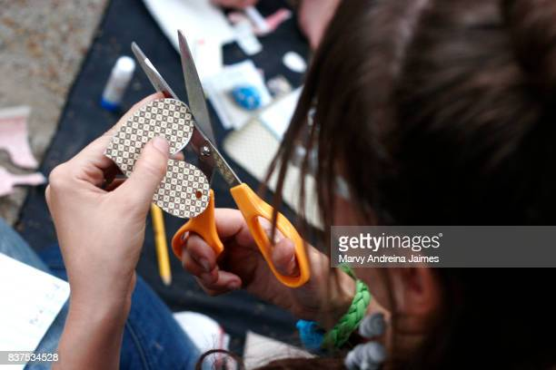 Caucasian woman cutting paper heart with scissors