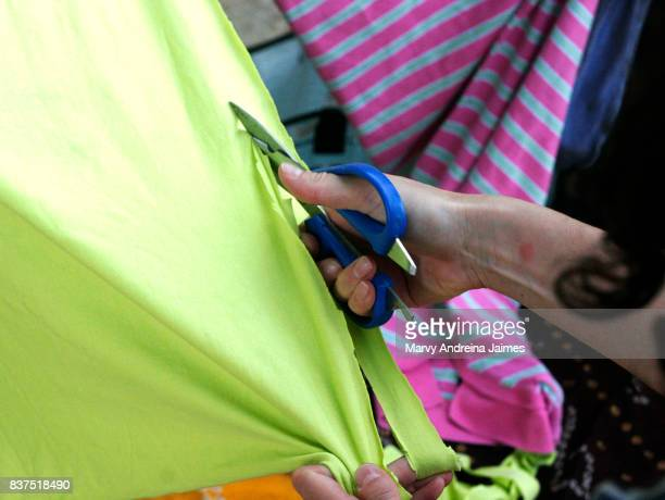Caucasian woman cutting textile with scissors