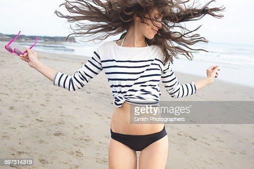 Caucasian woman dancing on beach