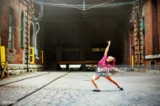 Caucasian woman dancing on cobblestone street