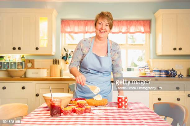 Caucasian woman decorating cakes in kitchen