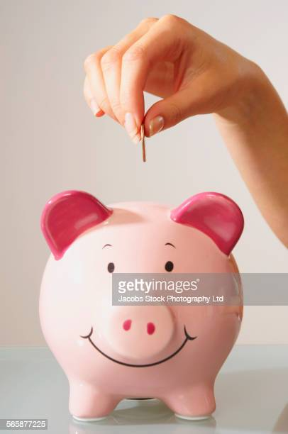 Caucasian woman depositing coin in piggy bank