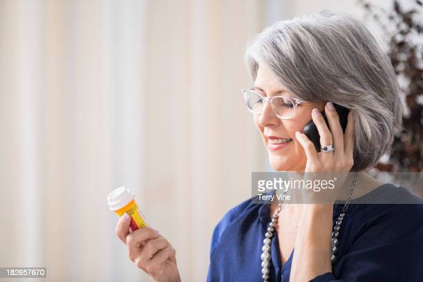 Caucasian woman discussing medication on cell phone