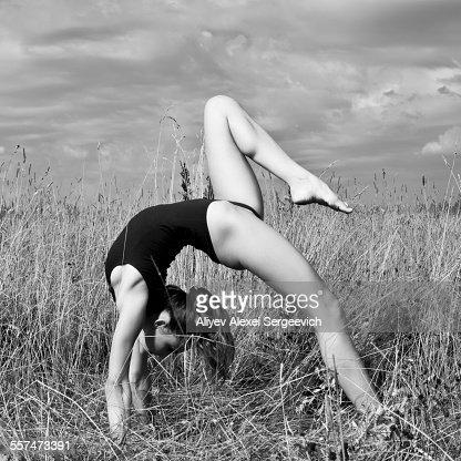 Caucasian woman doing backbend in tall grass