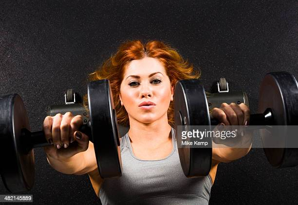 Caucasian woman doing chest presses with dumbbells in gym