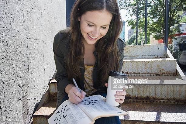 Caucasian woman doing crossword and drinking coffee on front steps