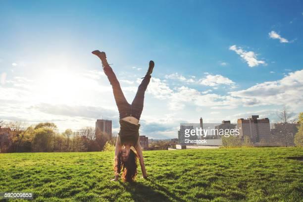 Caucasian woman doing handstand in urban park
