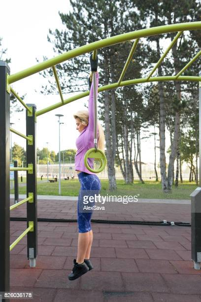 Caucasian woman doing intense calisthenics exercises on horizontal bar