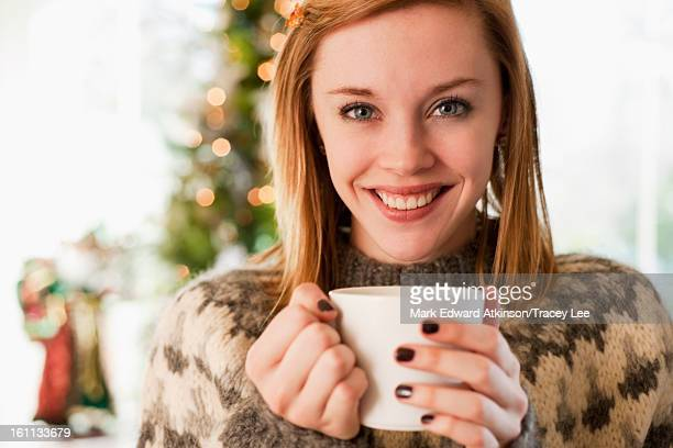 Caucasian woman drinking coffee at Christmas