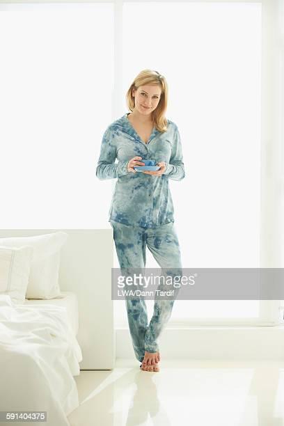 Caucasian woman drinking coffee in bedroom