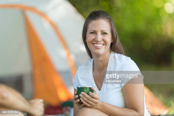 Caucasian woman drinking coffee outside tent