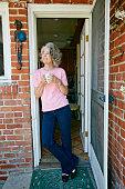 Caucasian woman drinking cup of coffee in doorway
