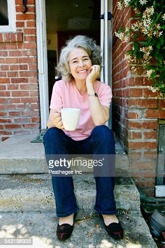 Caucasian woman drinking cup of coffee on front stoop