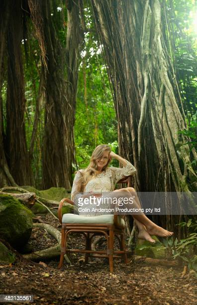 Caucasian woman drinking tea in chair below banyan trees