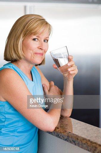 Caucasian woman drinking water in kitchen : Stock Photo