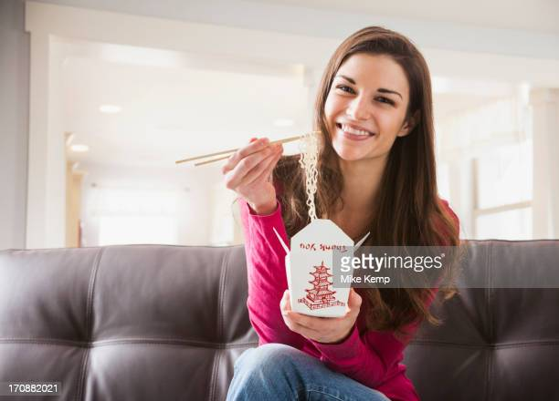 Caucasian woman eating Chinese food on sofa