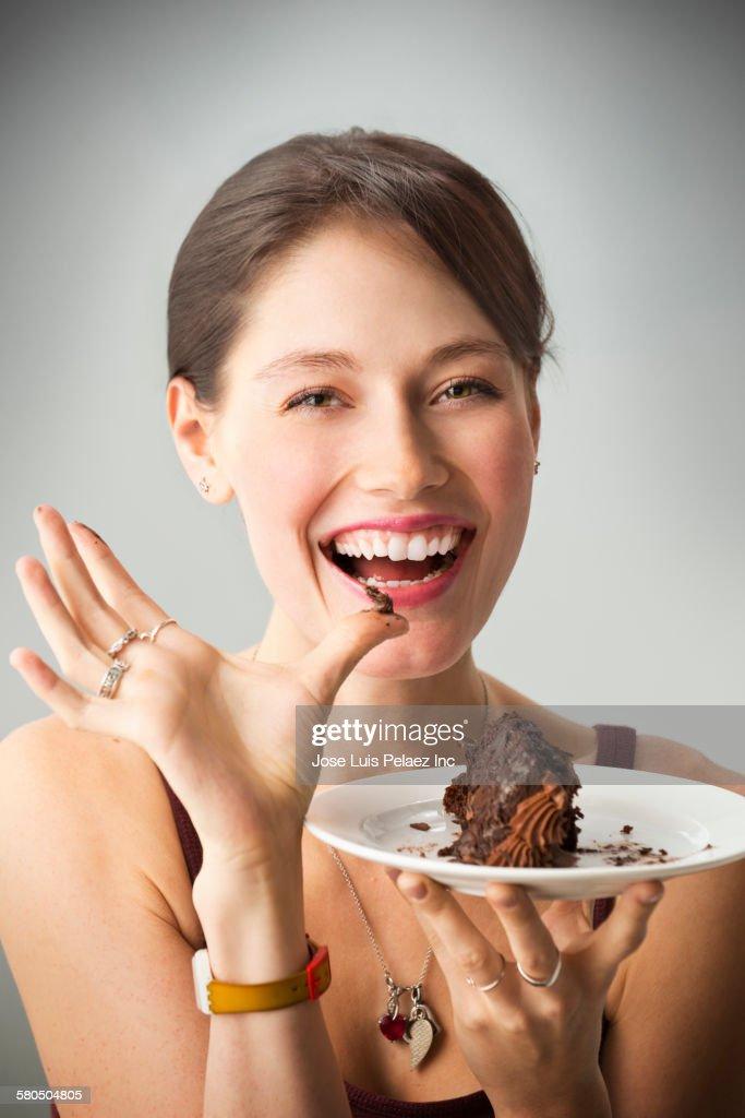 Caucasian woman eating chocolate cake