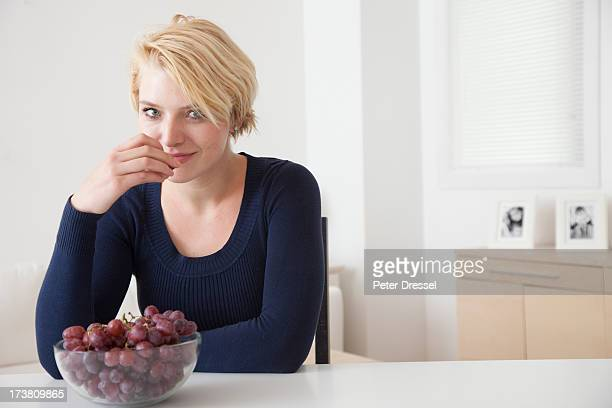 Caucasian woman eating grapes in kitchen