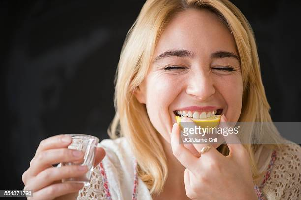 Caucasian woman eating lemon slice with liquor shot