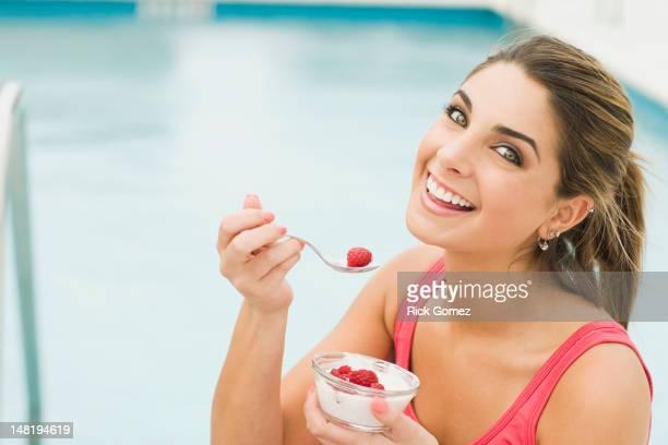 Caucasian woman eating yogurt and berries