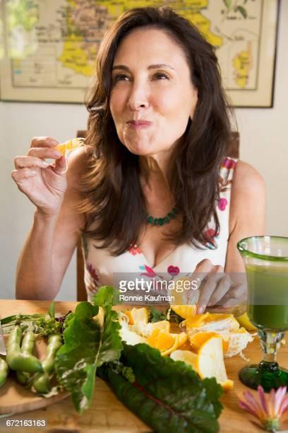 Caucasian woman enjoying eating oranges