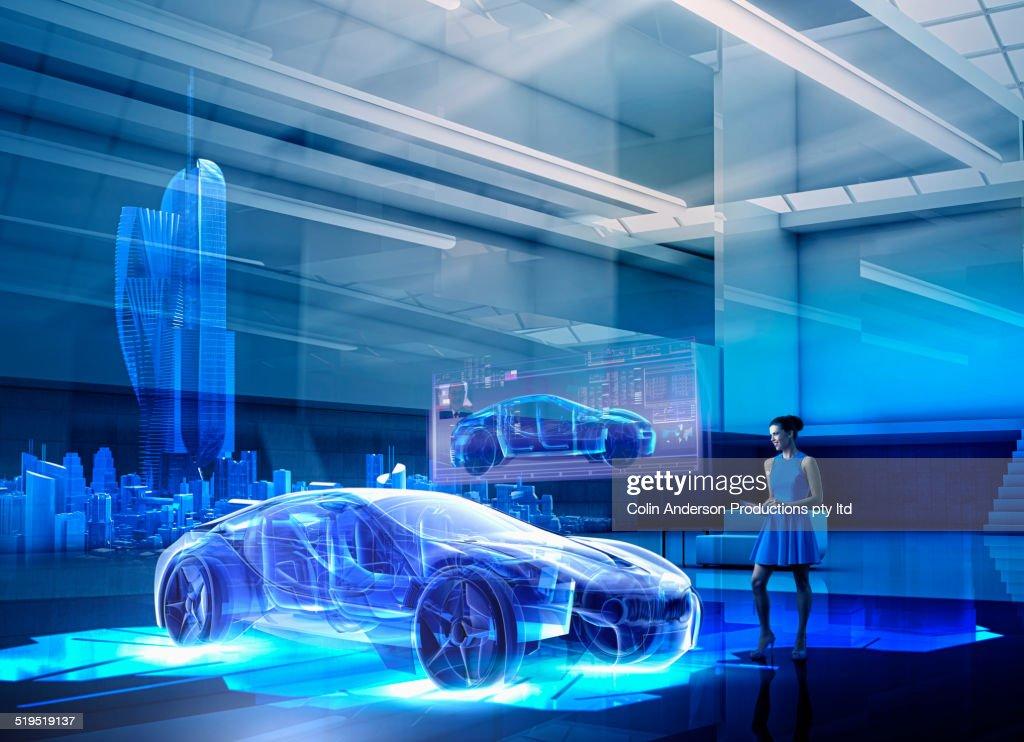Caucasian woman examining hologram of car : Stock Photo