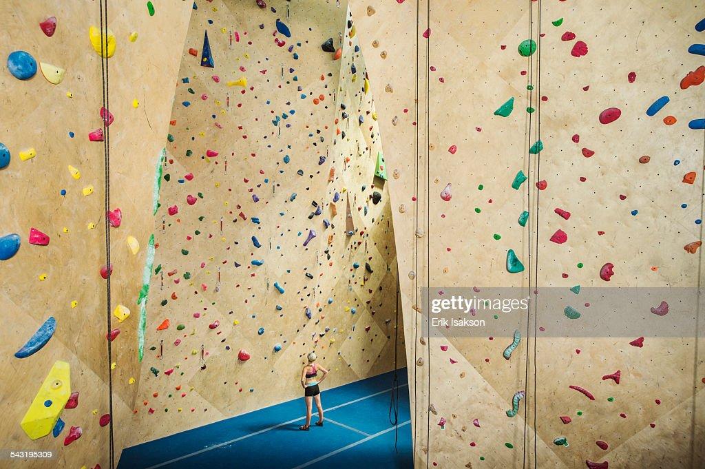 Caucasian woman examining indoor rock wall