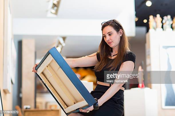 Caucasian woman examining painting in art gallery