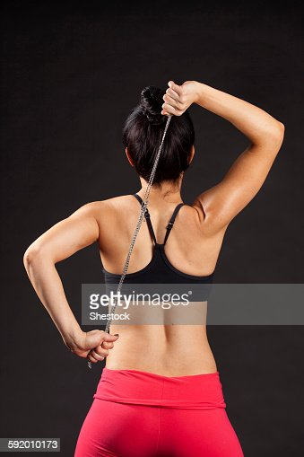 Caucasian woman exercising with rope behind back