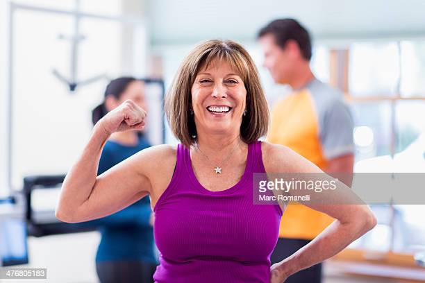 Caucasian woman flexing her muscles in gym