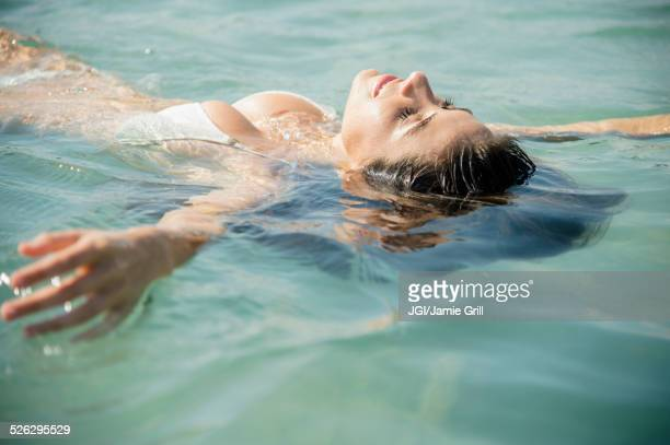 Caucasian woman floating in ocean