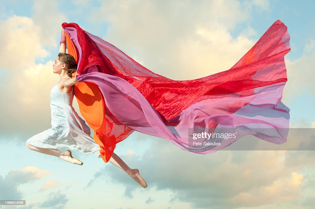 Caucasian woman floating through air with scarves