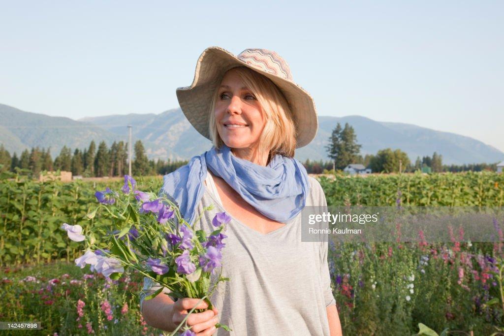 Caucasian woman gathering flowers in garden : Stock Photo