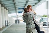 Caucasian woman greeting soldier boyfriend